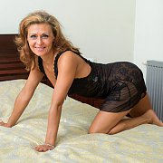 Mature Lady Crawling Onto The Bed In Black Nightie