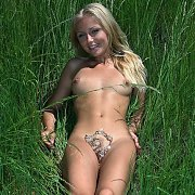 Nude Blonde Outdoors Laying In A Field Of Tall Grass