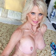 Stripteasing Blonde Mature On The Bed